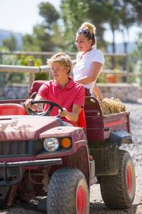 Young male and female grooms driving pick up with straw bales at rural stablesの写真素材 [FYI03566916]
