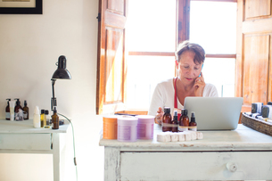 Woman talking on smartphone whilst using laptop in handmade soap workshop officeの写真素材 [FYI03566949]