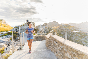 Woman on paved hilltop footpath, Mallorca, Spainの写真素材 [FYI03567240]