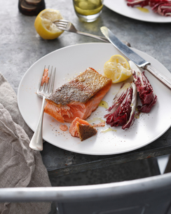 Crispy skin trout with lemon and radicchio on plate, close-upの写真素材 [FYI03567276]