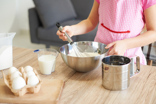 Young girl whisking ingredients together in bowl, mid sectionの写真素材 [FYI03567343]