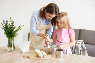 Mother helping daughter whisk ingredients together in bowlの写真素材 [FYI03567345]