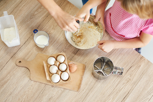 Mother helping daughter whisk ingredients together in bowl, overhead viewの写真素材 [FYI03567347]