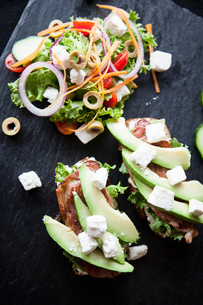 Meat, feta and avocado open sandwiches with salad on slateの写真素材 [FYI03567406]