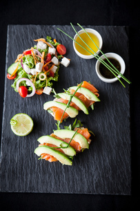 Smoked fish and avocado open sandwiches with salad and dipping sauces on slate, overhead viewの写真素材 [FYI03567410]