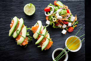 Smoked fish and avocado open sandwiches with salad and dipping sauces on slate, overhead viewの写真素材 [FYI03567413]