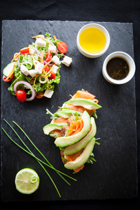 Smoked fish and avocado open sandwiches with salad and dipping sauces on slate, overhead viewの写真素材 [FYI03567414]