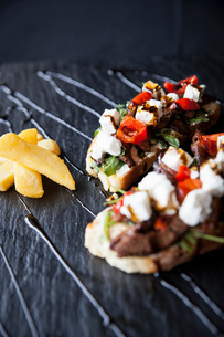 Meat, feta and tomato open sandwiches with chips and sauce garnish on slateの写真素材 [FYI03567417]