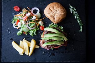 Overhead view of hamburger with avocado, side salad and chips on slateの写真素材 [FYI03567428]