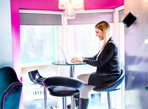 Businesswoman typing on laptop in officeの写真素材 [FYI03567450]
