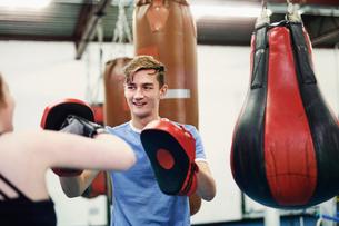 Female boxer training, punching teammate's punch mittの写真素材 [FYI03567481]
