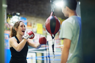 Young female boxer punching speed bag in gymの写真素材 [FYI03567518]