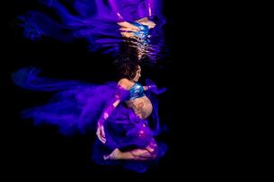 Pregnant woman draped in sheer fabric, underwater viewの写真素材 [FYI03567675]