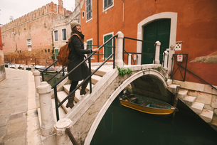 Woman crossing bridge over canal, Venice, Italyの写真素材 [FYI03567728]