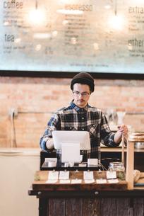Cashier using cash register in cafeの写真素材 [FYI03567751]