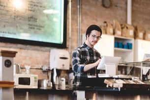 Cashier using cash register in cafeの写真素材 [FYI03567752]