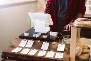 Cashier using cash register in cafeの写真素材 [FYI03567756]