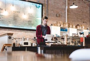 Cashier using cash register in cafeの写真素材 [FYI03567757]