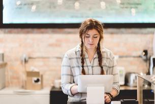 Cashier using cash register in cafeの写真素材 [FYI03567763]