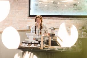 Cashier behind cash register in cafeの写真素材 [FYI03567765]