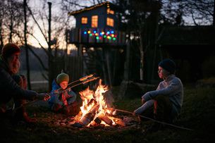 Mature woman and two sons toasting marshmallows on campfire at nightの写真素材 [FYI03567792]