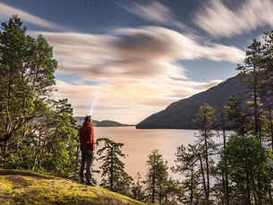 Male hiker looking up at evening stars, Comox Lake, Courtenay, Vancouver Island, British Columbia, Cの写真素材 [FYI03567820]