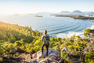 Elevated view of female hiker looking out from coastal forest, Pacific Rim National Park, Vancouverの写真素材 [FYI03567835]