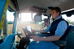 Young man driving tractor using global positioning systemの写真素材 [FYI03567864]
