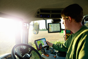 Young man driving tractor using touchscreen on global positioning systemの写真素材 [FYI03567868]