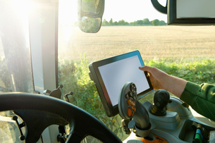 Farmer's hand driving tractor using touchscreen on global positioning systemの写真素材 [FYI03567869]