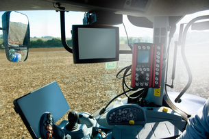 Farmer driving tractor using global positioning systemの写真素材 [FYI03567870]