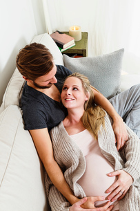 Pregnant mid adult couple touching pregnant stomach on sofaの写真素材 [FYI03567910]