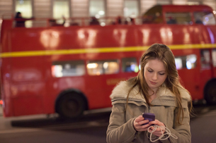 Young woman using mobile phone in street, London, UKの写真素材 [FYI03568011]