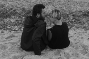 Young couple sitting on beach, face to face, rear viewの写真素材 [FYI03568097]