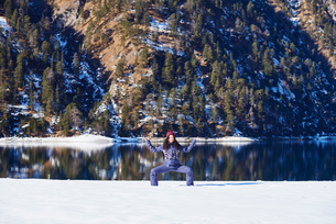 Woman in winter clothes practicing yoga pose on snowy lakeside, Austriaの写真素材 [FYI03568212]