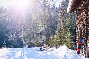 Woman practicing bow yoga pose by log cabin in snow,  Austriaの写真素材 [FYI03568213]