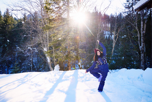 Woman in winter clothes practicing tree yoga pose in snow by forest, Austriaの写真素材 [FYI03568221]