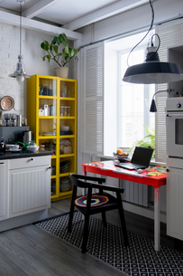 Kitchen with yellow cupboard and laptop on tableの写真素材 [FYI03568253]