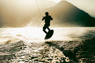 Silhouette of waterskier waterskiing, Maggiore lake, Verbania, Piedmont, Italyの写真素材 [FYI03568271]