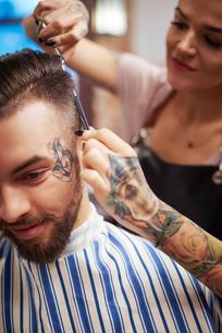 Hairdresser cutting customer's hairの写真素材 [FYI03568291]