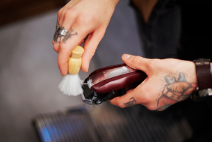 Man cleaning electric razor with shaving brushの写真素材 [FYI03568294]