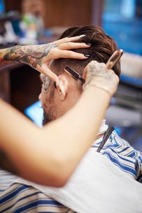 Hairdresser shaving customer's hair with straight razorの写真素材 [FYI03568295]
