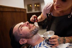 Woman applying shaving cream to man's beardの写真素材 [FYI03568304]