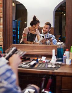 Mirror image of hairdresser showing customer magazineの写真素材 [FYI03568305]