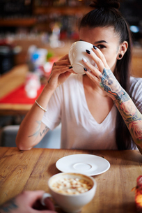 Tattooed woman in cafe drinking coffee looking at cameraの写真素材 [FYI03568331]