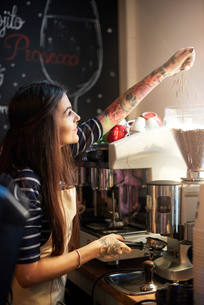 Barista filling machine with coffee beansの写真素材 [FYI03568336]