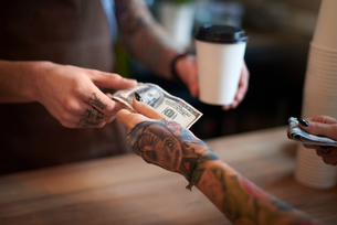 Customer paying for her coffee with cashの写真素材 [FYI03568351]