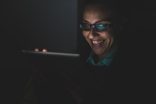 Young woman laughing while using digital tablet touchscreen in darknessの写真素材 [FYI03568543]