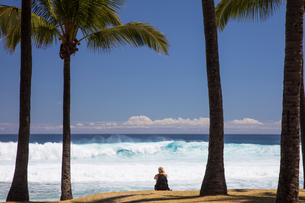 Female tourist sitting on beach looking out at Indian Ocean, Reunion Islandの写真素材 [FYI03568548]