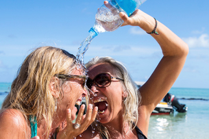 Mature female tourist pouring water over friend at beach, Reunion Islandの写真素材 [FYI03568589]